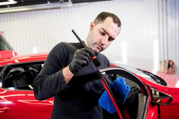 Autoservicemedewerker reinigt interieur met speciale borstel