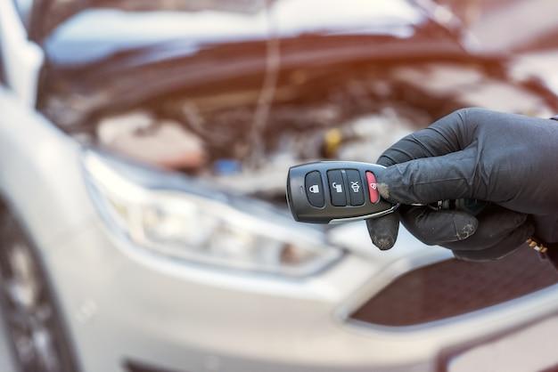 Autoservicemonteur houdt sleutels in de hand met auto op het oppervlak, open motorkap