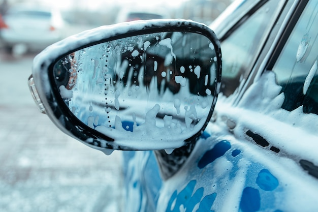Autoshampoo-schuim op de zijspiegel