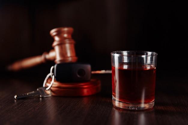 Autosleutel, houten rechter hamer en fles alcohol met glas close-up. drank rijden concept.