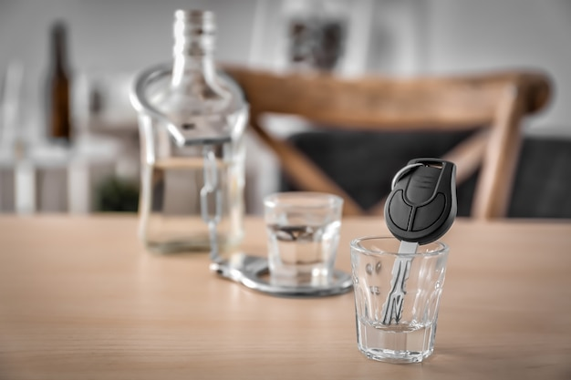 Autosleutel in glas met alcohol op houten tafel. niet drinken en rijden concept