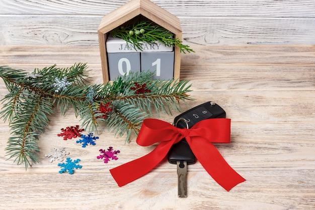 Autosleutel met kleurrijke boog en kalender, kerstboom, takken, sneeuwvlokken, op houten