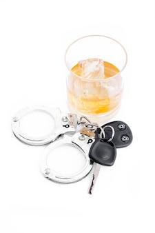 Autosleutel naast een whisky en een handboei