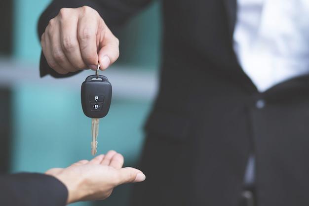 Autosleutel, overdracht van de zakenman geeft de autosleutel aan de andere vrouw