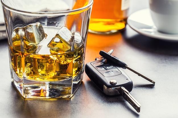 Autosleutels en glas alcohol op tafel in pub of restaurant.