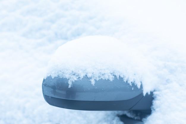 Autospiegel in de sneeuw. winterconcept. een deel van de auto.