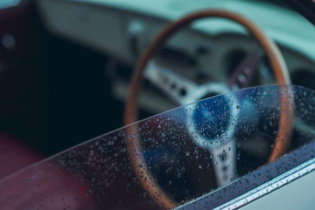 Autospiegel naast de bestuurder die nat, regenachtig is of waterdruppels op het glas heeft