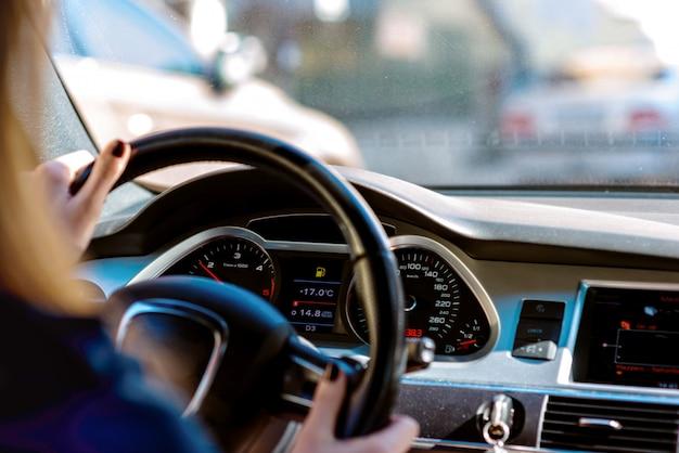 Autostuurwiel met bestuurdershanden op het