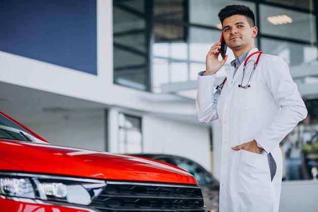 Autotechnicus met stethoscoop in een autotoonzaal praten aan de telefoon
