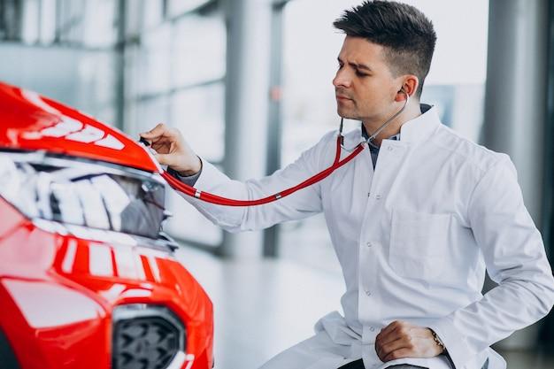 Autotechnicus met stethoscoop in een autotoonzaal