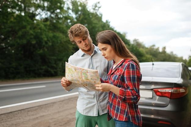 Autotoeristen die op kaart kijken, reizen over de weg. koppel op voertuig verdwaald, op zoek naar de juiste weg. man en vrouw op vakantie, autoreis
