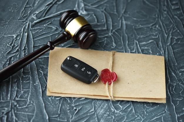 Autoveilingconcept - hamer en autosleutel op het houten bureau