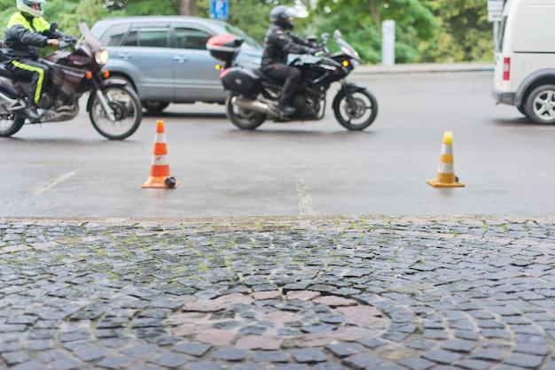 Autoverkeer op stenen weg in de oude stad, motorfietsen, auto's rijden langs de weg