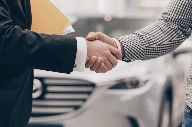 Autoverkoper die met een klant bij de dealer werkt
