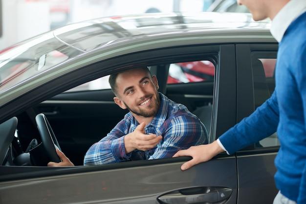 Autoverkoper en klant handdruk in autodealer.