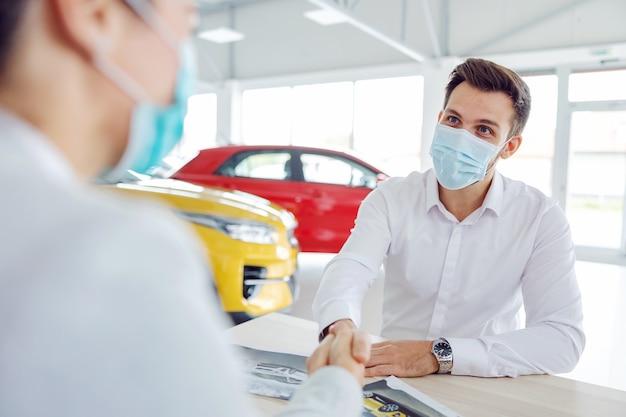 Autoverkoper en klant zitten aan de tafel in de autosalon en handen schudden omdat ze een deal hebben