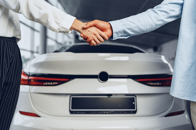 Autoverkoper en koperhanddruk bij autodealer tegen de achtergrond van een nieuwe auto