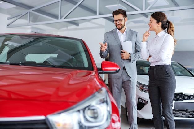 Autoverkoper houdt tablet vast en praat over autospecificaties en prestaties met een vrouw die een nieuwe auto wil kopen.