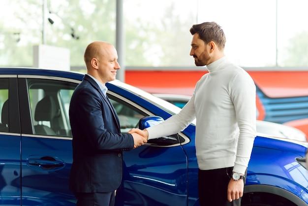 Autoverkoper overhandigen van de sleutels voor een nieuwe auto aan een jonge zakenman