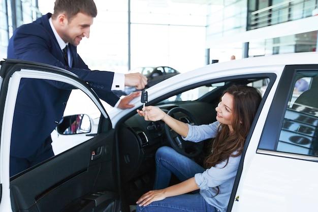 Autoverkoper verkoopt een auto aan tevreden klant in autodealer en overhandigt de sleutels