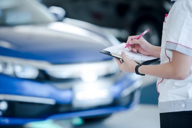 Autoverkopers registreren auto's op voorraad in de showroom van de verkoopvertegenwoordiger., aantekeningen voor nieuwe auto's op voorraad
