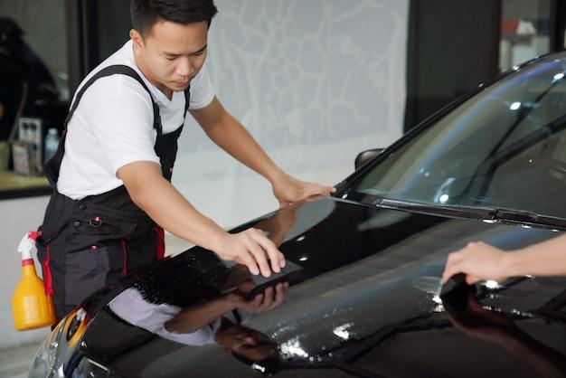 Autoverpakkingsspecialisten die beschermende film rechtmaken door vinylfolie of film op een zwarte auto te plaatsen.