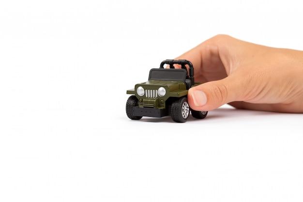 Autoverzekering. auto miniatuur bedekt door handen.