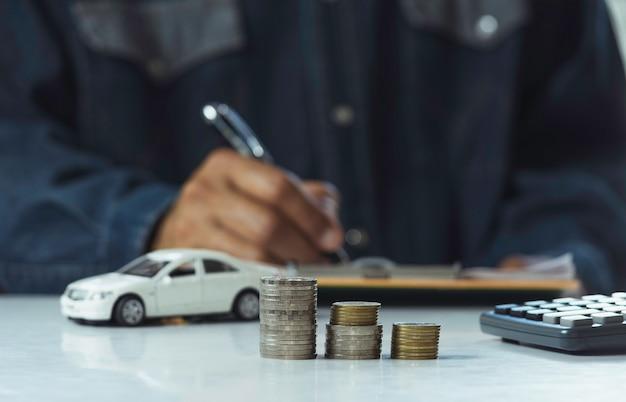 Autoverzekering en autodienst, zakenman met stapel van muntstukken en stuk speelgoed auto