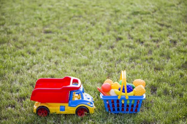 Autovrachtwagen en een mand met speelgoedfruit en groenten