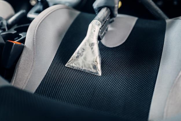 Autowasdienst, mannelijke werker verwijdert stof en vuil