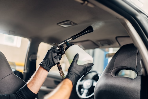Autowasdienst, mannelijke werknemer in handschoenen met speciale spray.