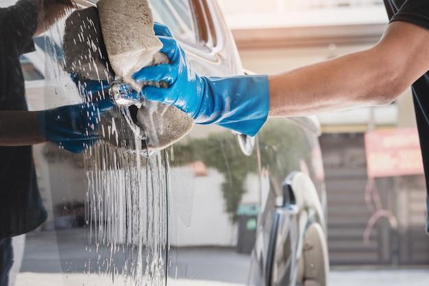 Autowaspersoneel draagt blauwe rubberen handschoenen met een spons die is bevochtigd met zeep en water om de auto te reinigen.