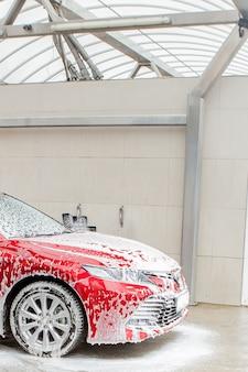 Autowassen met schuim in autowasstation. carwash. wasmachine op het station. auto wassen concept. auto in schuim.