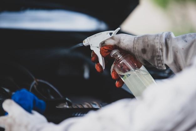 Autowasserettearbeider die een witte eenvormig dragen die zich een spons bevinden om de auto in het autowasserettecentrum schoon te maken, concept voor de autozorgindustrie.