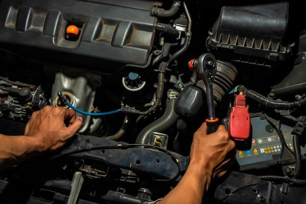 Autowerktuigkundige die aan de motor in de garage kijkt. service motor reparatie.