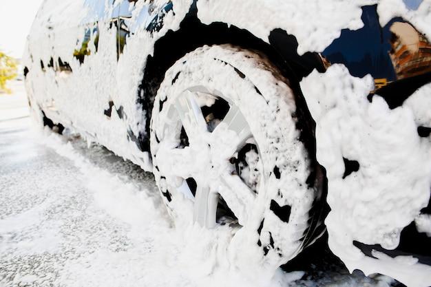 Autowiel bedekt met zeepschuim