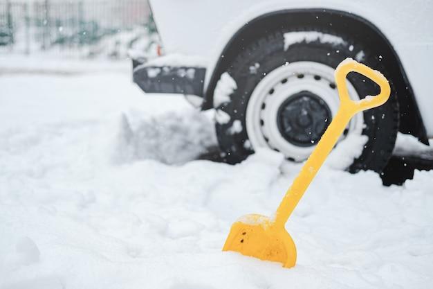 Autowiel in sneeuw en een schop.