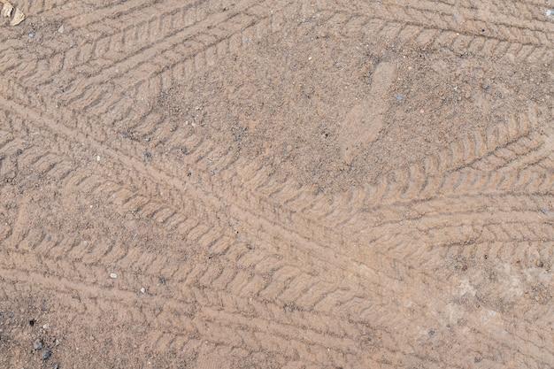 Autowiel op een landweg op de bruine droge grondgrond