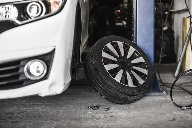 Autowiel verwisselen in auto, autoservice met opgeheven voertuig, servicecentrum, banden verwisselen