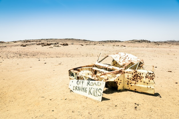 Autowrak in de woestijn van namibië - gevaarsteken voor het verlaten van de wegen