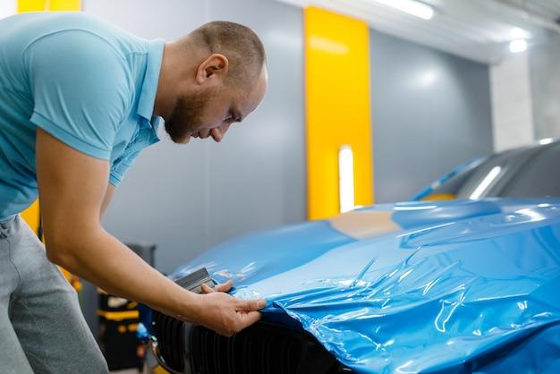 Autowrapper legt beschermfolie of film op de motorkap