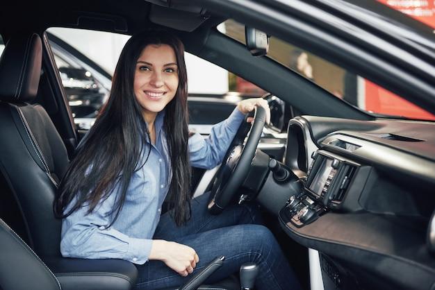 Autozaken, autoverkoop, consumentisme en mensenconcept - gelukkige vrouw die auto van dealer in autoshow of salon nemen