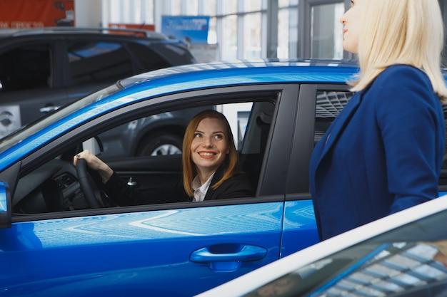 Autozaken, autoverkoop, consumentisme en mensenconcept - gelukkige vrouw met autodealer in autoshow of salon