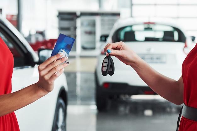 Autozaken, autoverkoop, overeenkomst, gebaar en mensenconcept - sluit omhoog van handelaar die sleutel geven aan nieuwe eigenaar in auto toon of salon