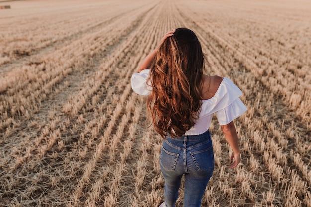 Autumn girl dat van aard op het gebied geniet. schoonheid meisje buitenshuis verhogen handen in zonlichtstralen