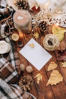 Autumn mood blanco vel papier op een houten tafel met bladeren, kaarsen en een plaid.