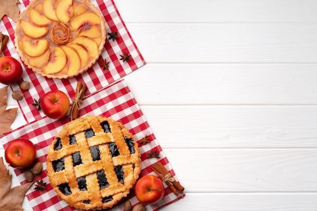 Autumn thanksgiving taarten op wit houten bord versierd met droge bladeren en kaneelstokjes, bovenaanzicht