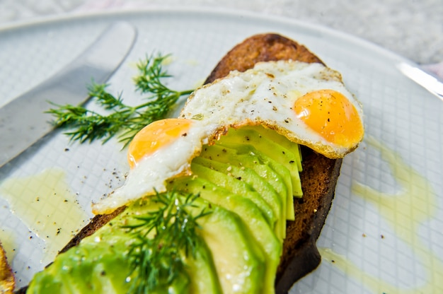 Avacado-sandwich met ei op toost van zwart brood.