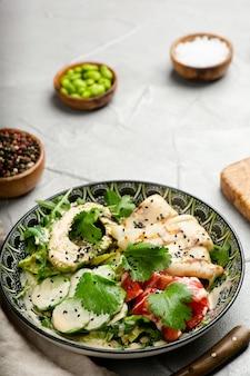 Avacadosalade met pijlinktvis en verse groentenclose-up met exemplaarruimte