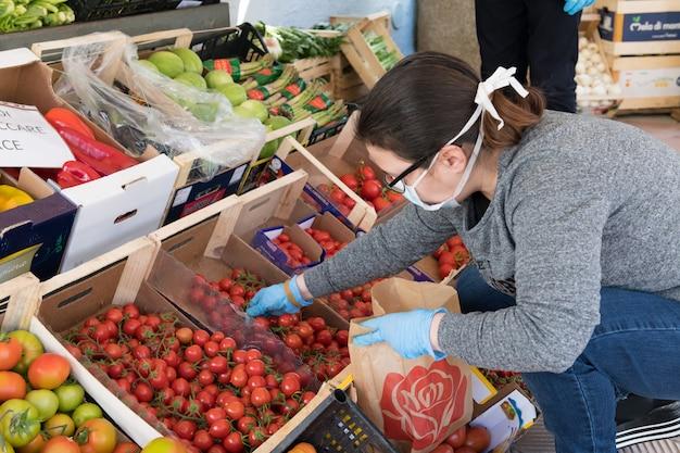 Avetrana, italië, - marth, 13, 2020. een italiaanse groenteboer die een klant bedient met een medisch masker en handschoenen aan de gezondheidsnormen tijdens de epidemie van het coronavirus.